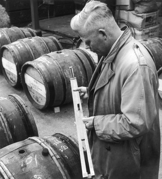 A customs Official checks the level of wine in an imported barrel. Photograph by Heinz Zinram
