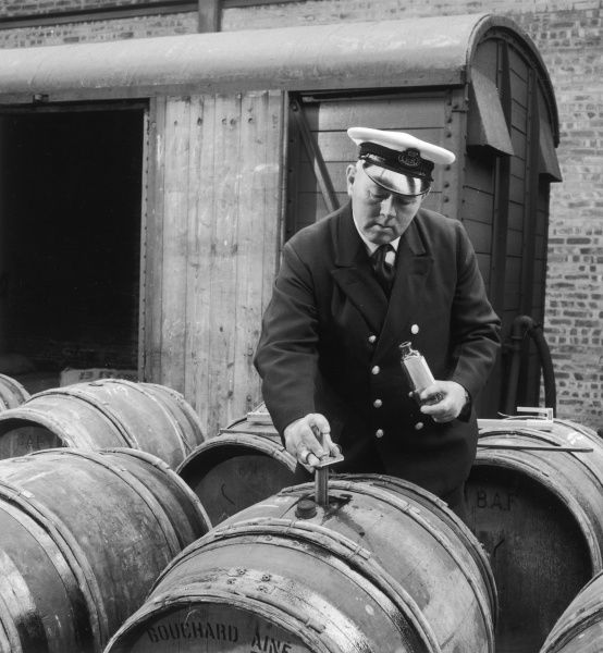 A customs official tests wine from an imported barrel of wine. Photograph by Heinz Zinram