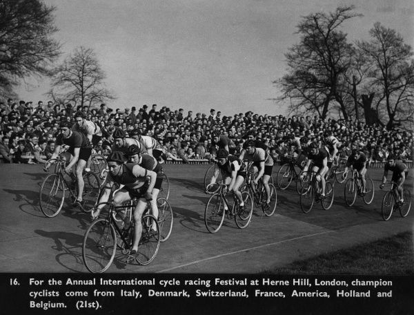 A cycle racing event, part of an annual international festival, at Herne Hill, south London, involving champion cyclists from Italy, Denmark, Switzerland, France, America, Holland and Belgium. They are watched by a crowd of spectators.  circa 1940s