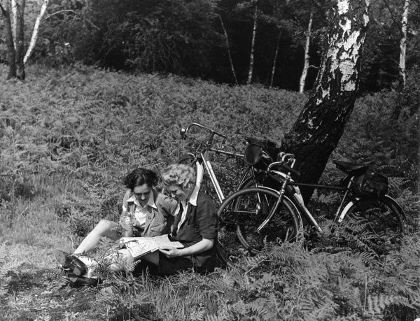 Two young women cyclists rest awhile and study a map, near High Beach, Epping Forest, Essex, England. Date: 1930s