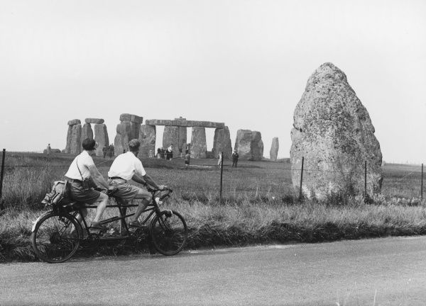A man and a woman cycle past Stonehenge on a tandem bicycle
