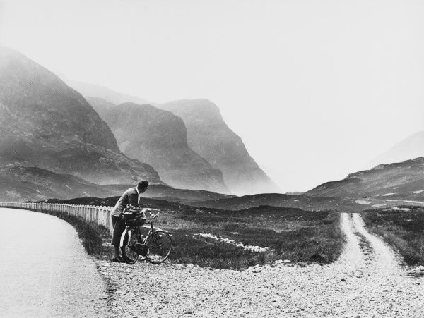 A touring cyclist takes in the breathtaking Scottish scenery at the Old Road, Pass of Glencoe, Invernes-shire