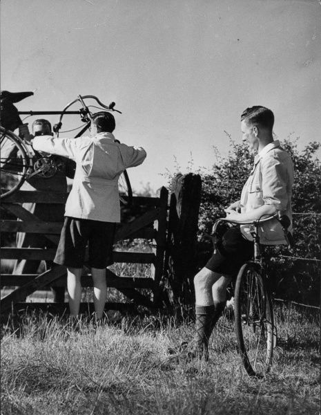Cycling 'off the beaten track' often means having to negotiate a gate or stile, but that all adds to the fun, as these young men demonstrate! Date: 1930s