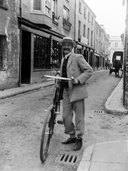 A cyclist with his bicycle smiles at the camera in Bridge Street, Haverfordwest, Pembrokeshire, Dyfed, South Wales