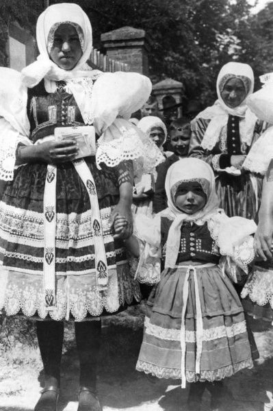 These bridesmaids, at a village near Prague, Czechoslovakia, made a pretty picture, in their traditional handworked costumes. Date: 1930s