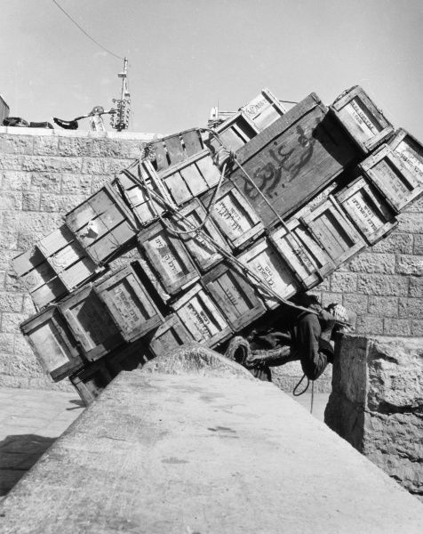A man carrying a heavy load of wooden boxes through Damascus Gate, Jerusalem, Israel. Date: late 1960s