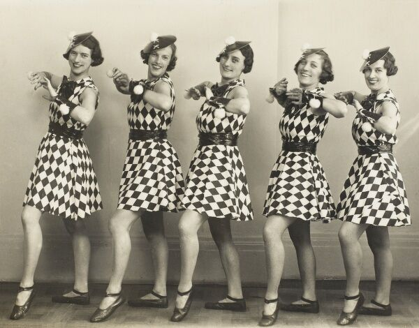 A line of five dancing girls in summer clothing, showing off rather shapely legs and ankles!