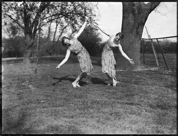 Two girls dancing artistically together in the style of Isadora Duncan