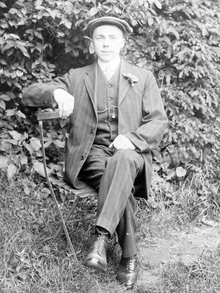 A dapper young man sitting on a folding steel chair in a garden, Mid Wales. He is wearing a three-piece suit with a flower in his buttonhole, and a flat cap