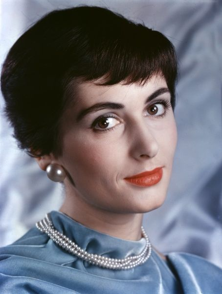 A 'girl in pearls' with short, black hair, very dark eyebrows & brown eyes, smiles knowingly. She wears large, pearlised button earrings