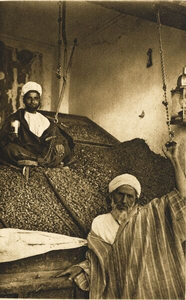 A stall selling dates - Marrakesh, Morocco. The trader sits halfway up the immense pile of the dried fruit, which he can weigh on the suspended scales alongside his perch