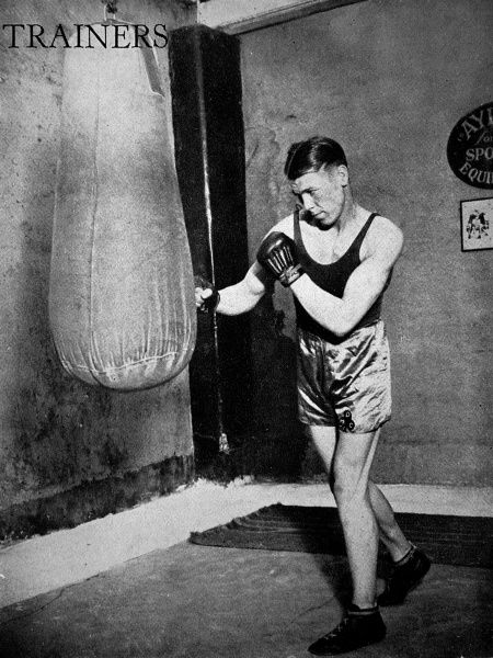 Photograph showing Dave McCleave, then British welterweight champion, using a punch bag in a gym, 1936