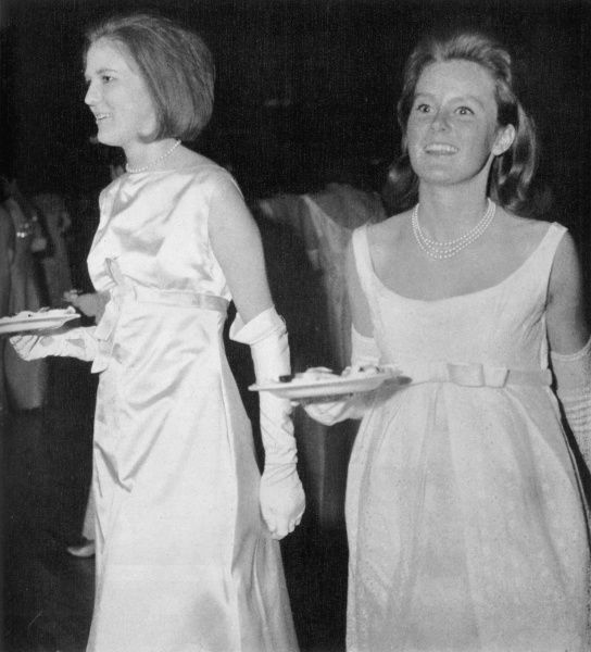 Miss Diana Goedhuis, daughter of the Dutch civil air attache and her cousin Veronica Henderson, both dressed in white ballgowns carrying cake at Queen Charlotte's Ball