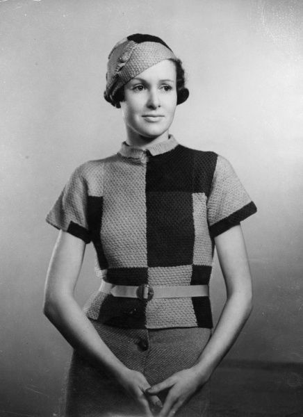 Hand-knitted 'Chessboard' jumper with short sleeves & the new demure little collar is composed of large different coloured squares. Worn with a belt & matching brimless hat