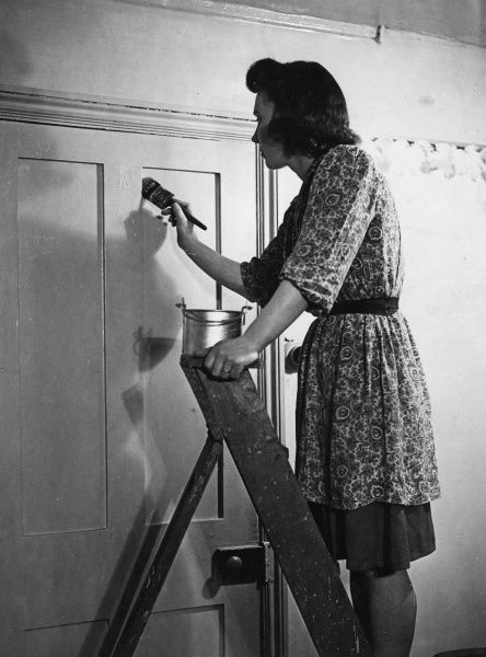 A woman, wearing a floral over dress, stands on a step ladder to give a door a fresh coat of paint