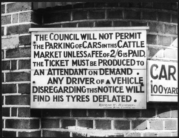 A sign in Spalding, Lincolnshire, warning that any motorists who park their cars in the cattle market without paying the 2/6 fee will have their tyres deflated