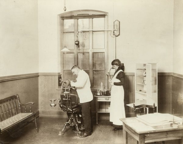 A dentist and his nurse give a schoolboy his treatment, 1910 Date: c. 1910