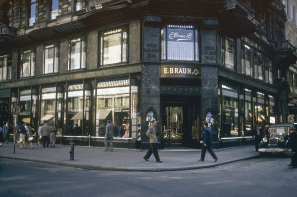 A large department store, E Braun & Co, on the corner of a street in Vienna, Austria, with people out shopping. Date: 1953