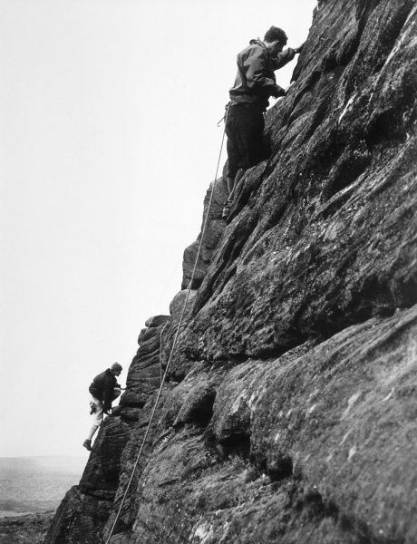 Two climbers make their way up a steep rockface. Date: 1950s