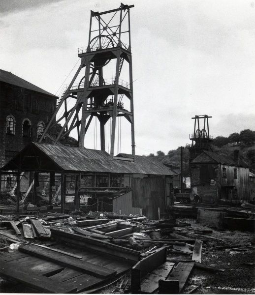 View of the derelict Tirpentwys Colliery near Pontypool in South Wales. The foreground is littered with pieces of wood, including an empty coffin which has broken apart. The colliery closed in 1969