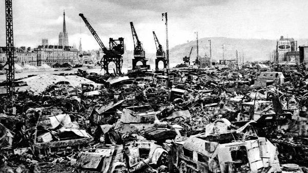 Photograph showing the scene of destruction at Rouen Docks, France, caused by Allied bombing raids on German positions, 1944. In the foreground of this image are a large number of German car and armoured vehicles wrecked and burnt in the bombing