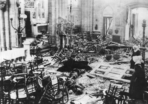 Devastation inside a church in Ostend, Belgium, during the First World War. Nuns stand on the right, looking at the bodies of women, and a jumble of wooden chairs. Date: circa 1914