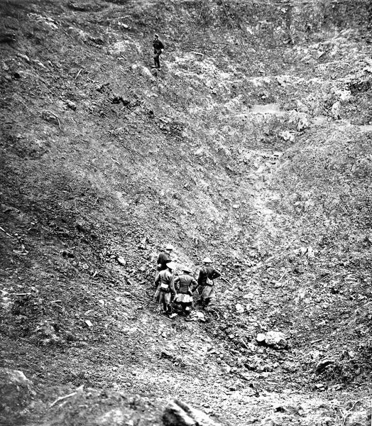A photograph of several British soldiers walking through the enormous crater left behind by the explosion of a large land-mine at High Wood, during the Somme offensive of 1916