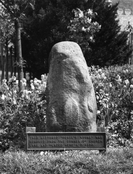 The historic 'Devil's Stone', situated near the church at Newington, Kent, England. This is probably an ancient 'mark- stone'. Date: BC
