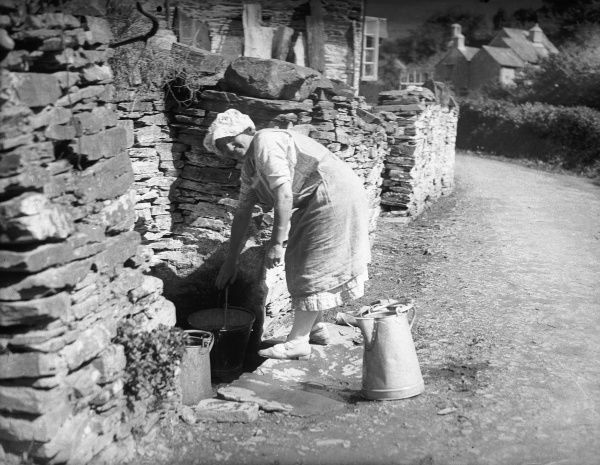 A country lass fetches water from the well in Milton Coombe, South Devon, England