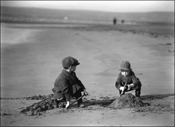 A Devon Beach Scene. Two young boys in coast and caps build a sandcastle. Photograph by Ralph Ponsonby Watts