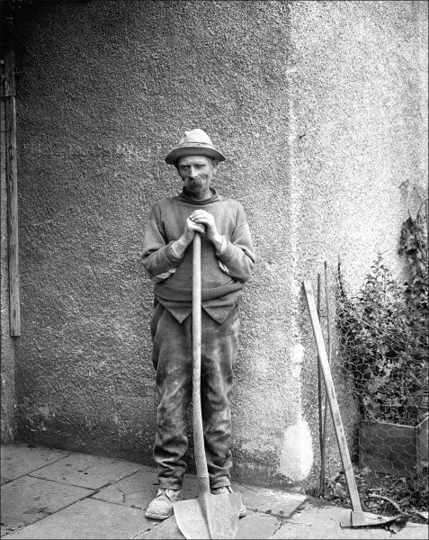 The gardener of a large house in Devon stops to have a rest. He is leaning on his spade, and has left a hoe leaning up against the wall