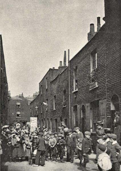 Devonshire Place (or perhaps Devonshire Place Mews), Lisson Grove, near Paddington, London. A crowd - mostly children with a few adults - has gathered. Someone holds a placard aloft