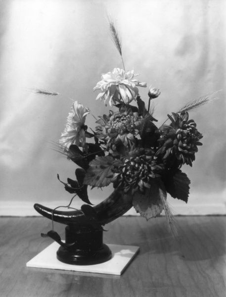 'Diamond' flower arrangement, made up of chrysanthamums, with wild barley and beech leaves. Date: 1950s
