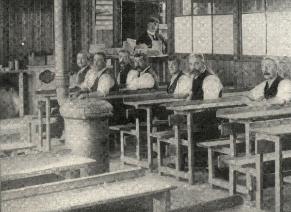 A few men are seated in the dining Hall at Laindon Labour Colony, near Dunton, Essex. An iron stove stands in the centre. The colony was established in 1904 by the Poplar Poor Law Union as an alternative to the workhouse for able-bodied men