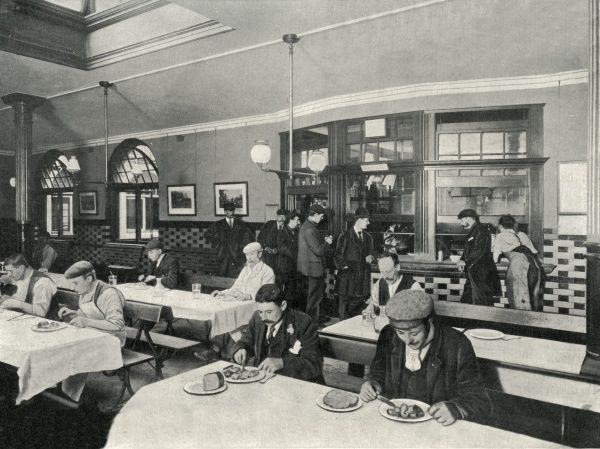 View inside the dining room of a Rowton House in Hammersmith, West London, with male inmates eating at tables and queueing to be served