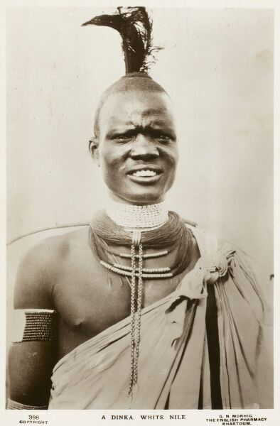 A fine portrait photograph of a man of the Dinka Tribe, Sudan, showing ritual scarification on the chest, headdress, neck beads and wound torc