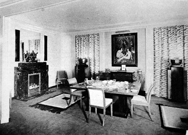 The dining room: furniture in coromandel and walnut, giving a keynote of black and yellow. A black marble mantlepiece and lighting urns on pedestals. The new British furniture, a complete home in the modern manner. An exhibition at Waring and Gillow