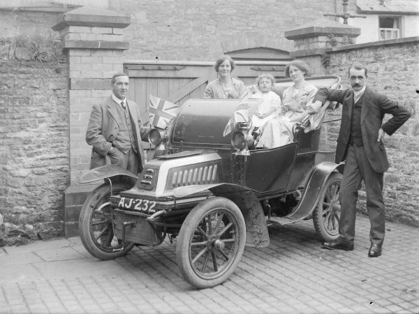 A proud family with their 1903-4 De Dion Bouton motor car, registration AJ 232, in a back yard in Crickhowell, Powys, Mid Wales