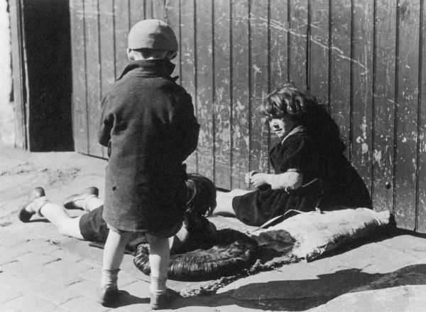 Working Class children sunbathing on dirty cushions on a London street
