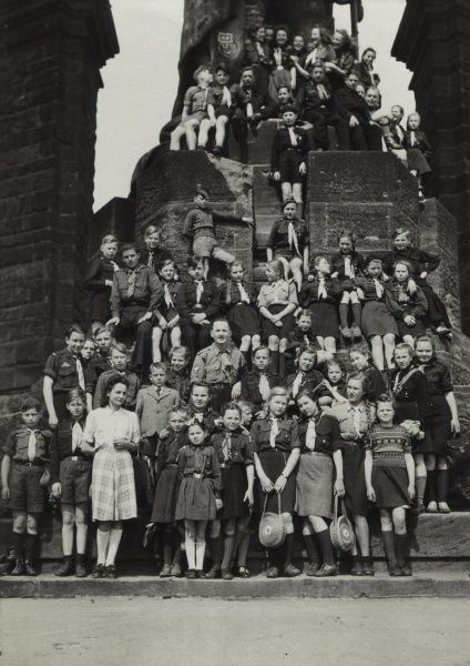A large group of displaced Lithuanian Scouts and Guides and their leaders sitting on a monument in Germany. 1940s