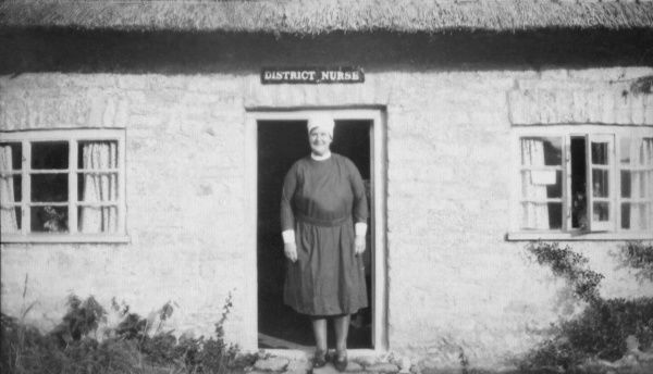 A District Nurse standing in the doorway of her single-storey thatched cottage