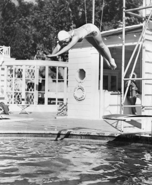 A young woman spring off the diving board into the swimming pool at the Hotel Miramar, Santa Monica, California, USA. Date: 1940s