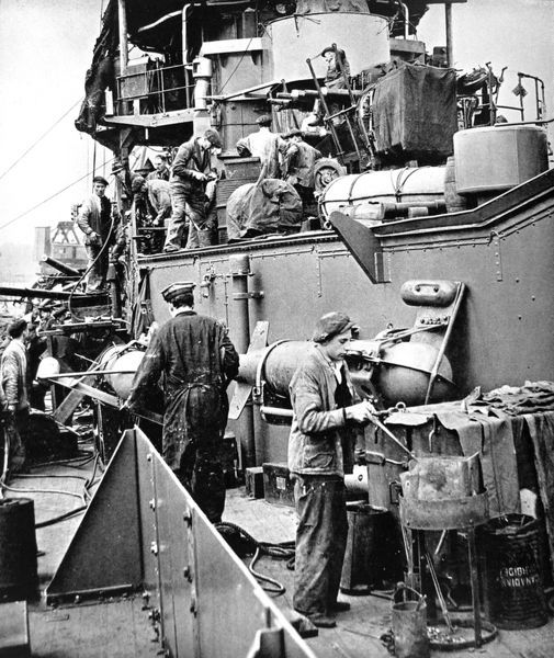 Photograph showing dockyard workers, including a rivetters' boy working with a portable forge, refitting HMS 'Coventry' during the Second World War, 1940. HMS 'Coventry' was a Royal Navy anti-aircraft cruiser of 4290 tons
