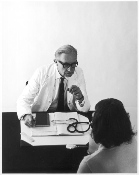 A doctor sits at his desk talking to a patient
