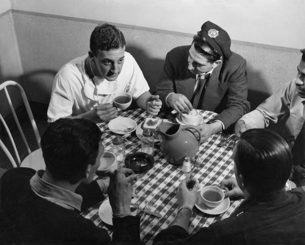 A doctor relaxes with ambulance staff in the hospital canteen after attending to an injured man. They discuss the man's chances of survival