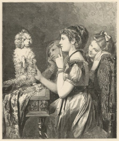 Three young girls train a small white dog who sits obediently on the table in front of them. One of the girls takes the dog's paw and orders him to be quiet by holding her finger against her lips