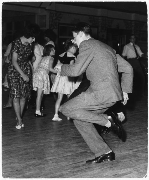 A dapper young man in a suit twists on the dancefloor
