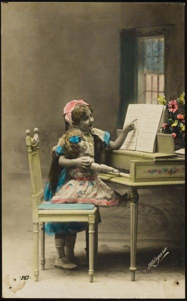 A little girl attempts to give her doll a piano lesson