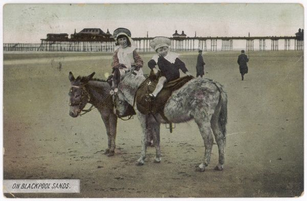 Boy and girl on donkeys at Blackpool, Lancashire