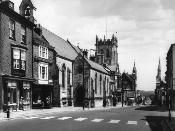 A glimpse of the High Street, Dorchester, Dorset, England, an important town in Roman Britain and a busy town today. Date: 1950s